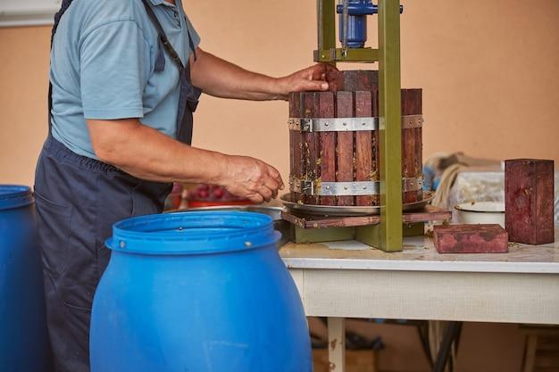 Bijgesneden foto van een werkende man die een wijnpers gebruikt om het druivensap te persen