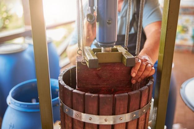 Bijgesneden foto van een wijnmakerij die druk uitoefent op een wijnpers om de druiven uit te persen