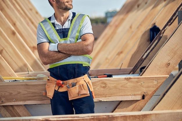 Bijgesneden foto van een zelfverzekerde man die een gereedschapsriem draagt terwijl hij met gekruiste armen in de buurt van een bouwwerk staat