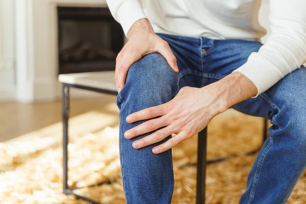 Bijgesneden foto van een zittende jongeman die lijdt aan gewrichtspijn op kantoor