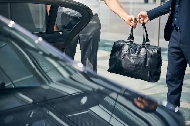 Bijgesneden foto van een zwarte tas die wordt doorgegeven van bestuurder aan passagier die bij de auto staat
