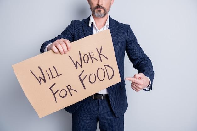 Bijgesneden foto van ernstige arme dakloze ontslagen man lijden financiële crisis verloren werk baan houden plakkaat zoeken werk voor voedseluitwisseling directe vinger kaart dragen pak geïsoleerde grijze achtergrond