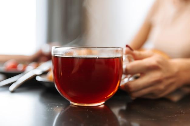 Bijgesneden foto van europese vrouw zittend aan tafel in flat, met hete thee in glas