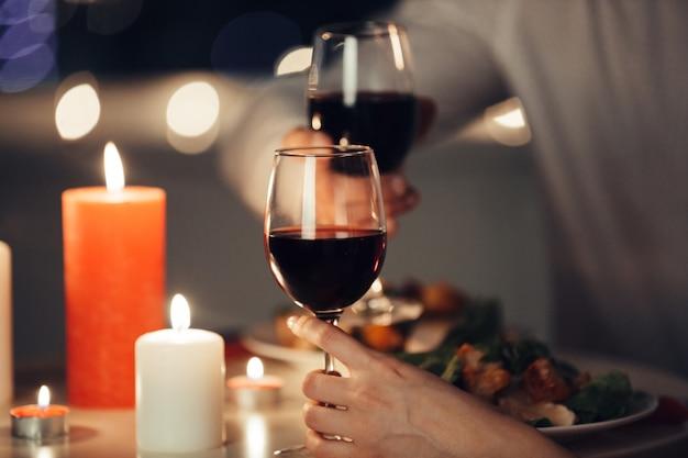 Bijgesneden foto van geliefden met een romantisch diner thuis