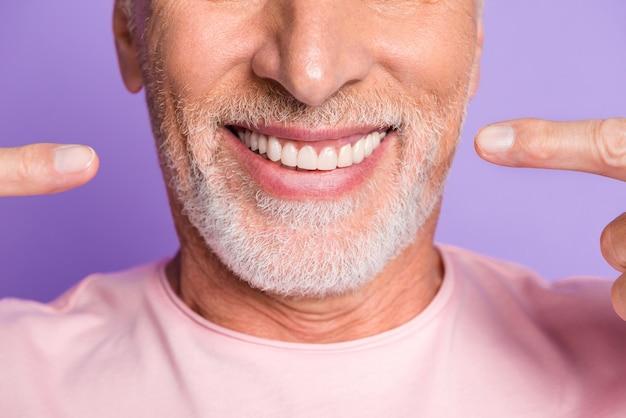Bijgesneden foto van gepensioneerde oude man gezicht mond directe vingers witte glanzende tanden dragen roze t-shirt geïsoleerd violet kleur achtergrond