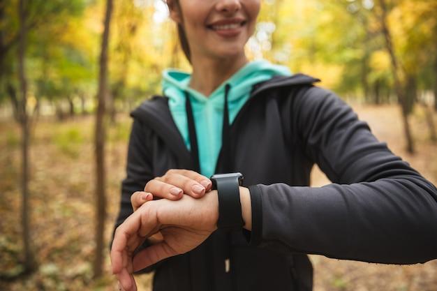 Bijgesneden foto van geweldige jonge mooie fitness vrouw buiten in het park horloge klok kijken.