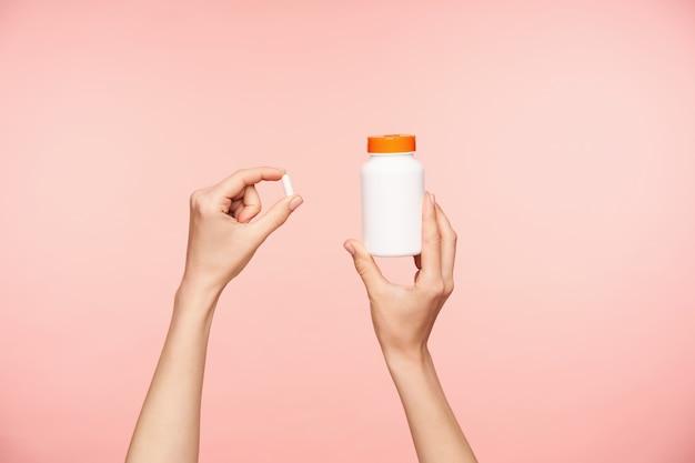 Bijgesneden foto van goed verzorgde handen van opgeheven vrouw met witte pil en fles met oranje deksel, vitamines nemen terwijl poseren op roze achtergrond