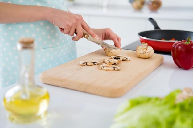 Bijgesneden foto van huisvrouw handen champignons snijden nieuw recept zoals ochtend koken lekker diner voorbereiding familie man kinderen wit licht keuken binnenshuis