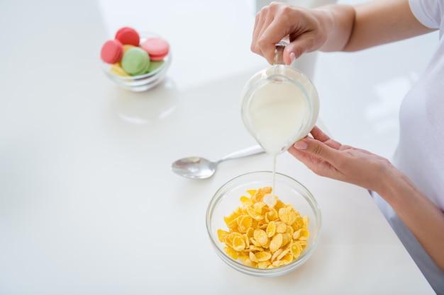 Bijgesneden foto van huisvrouw handen met gieten melkkannetje koken ontbijt cornflakes gezond eten concept dieet houden negeren snoep wit licht keuken binnenshuis
