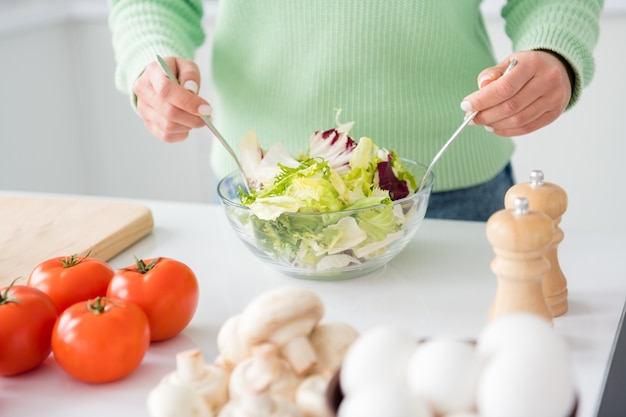 Bijgesneden foto van huisvrouw houdt twee lepels vast en mengt salade