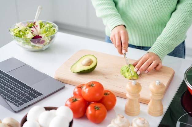 Bijgesneden foto van huisvrouw met mes dat verse avocado snijdt