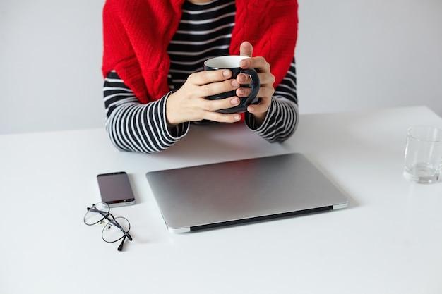 Bijgesneden foto van jonge stijlvolle vrouw freelancer kopje thee in haar handen houden tijdens de voorbereiding voor zakelijke bijeenkomst, zittend aan tafel met moderne laptop en smartphone
