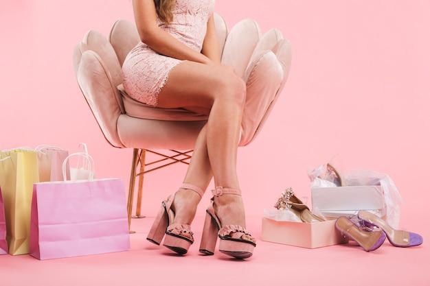 Bijgesneden foto van jonge vrouw in jurk met gezonde benen gekruist zittend in een stoel in de buurt van boodschappentassen en schoenen dozen, geïsoleerd over roze muur