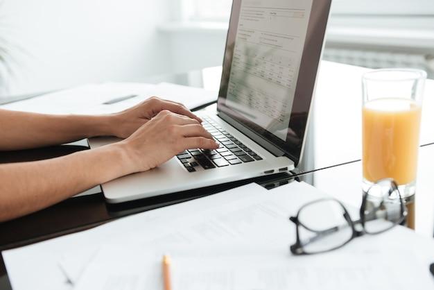 Bijgesneden foto van jonge vrouw met glas sap typen door laptop.