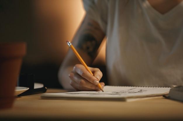 Bijgesneden foto van jonge vrouw ontwerper schrijven van aantekeningen.