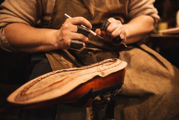 Bijgesneden foto van jongeman schoenmaker