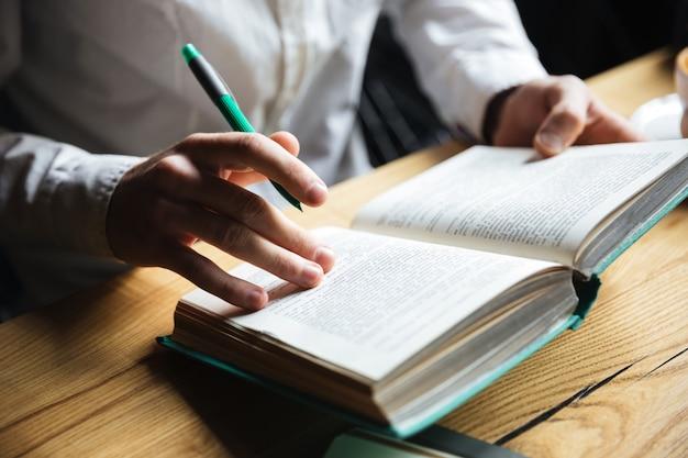 Bijgesneden foto van man in wit overhemd leesboek