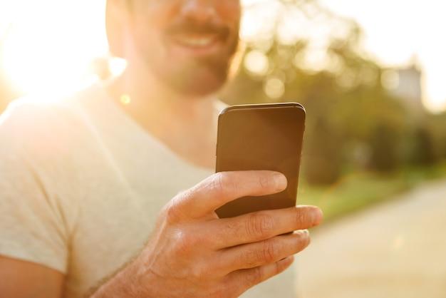 Bijgesneden foto van vrolijke blanke man in vrijetijdskleding glimlachend en met behulp van zwarte smartphone om te chatten, tijdens het wandelen in het groene park