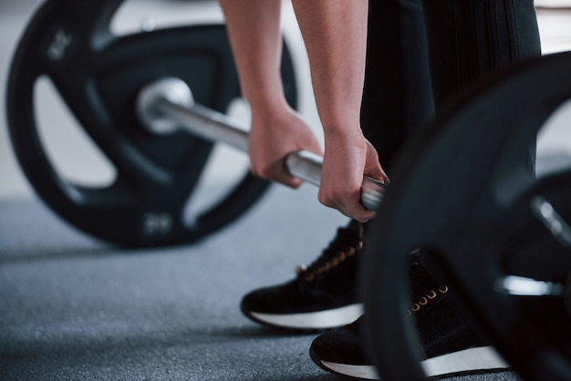 Bijgesneden foto van vrouw doet kraken met barbell in de sportschool