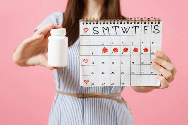 Bijgesneden foto van vrouw in blauwe jurk met witte fles met pillen, vrouwelijke periodenkalender, menstruatiedagen geïsoleerd op de achtergrond controleren. medische gezondheidszorg gynaecologische concept. ruimte kopiëren.