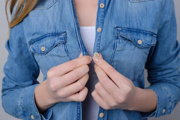 Bijgesneden foto van vrouw in jeansoverhemd met knopen