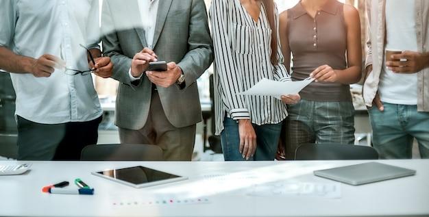 Bijgesneden foto van zakenmensen die samen staan in het moderne kantoor zakelijke bijeenkomst