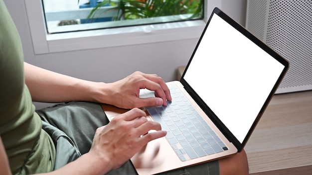 Bijgesneden geschoten man met laptop in de woonkamer.