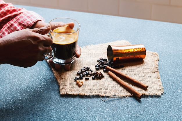 Bijgesneden hand met een kopje koffie met ingrediënt.
