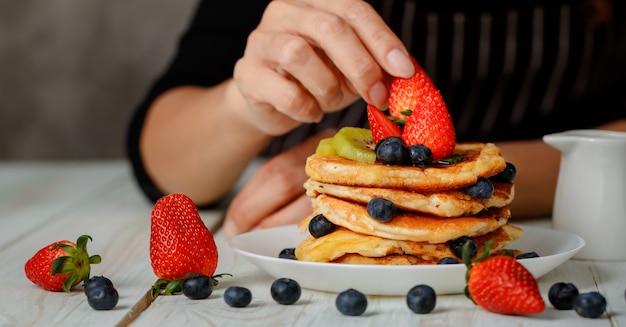 Bijgesneden hand van huisvrouw die pannenkoeken bereidt om voedsel voor het gezin te zijn, met bovenop fruit, aardbeien, kiwi en bosbessen.
