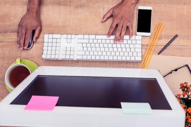 Bijgesneden hand zakenman aan het werk op computer aan tafel in kantoor