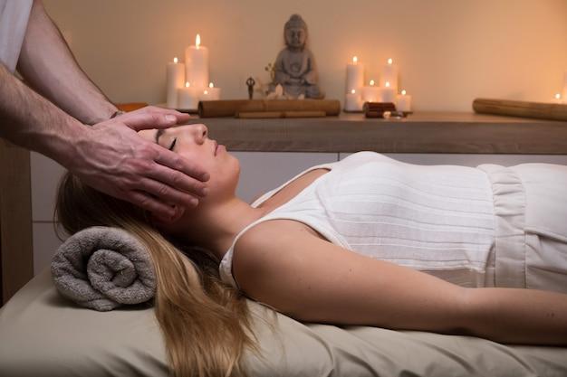 Bijgesneden handen van therapeut reiki uitvoeren op vrouw