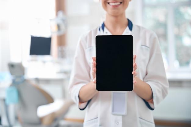 Bijgesneden hoofd van een gelukkige vrouw die in de buurt van een moderne tandartsstoel staat en een digitaal touchpad-scherm toont