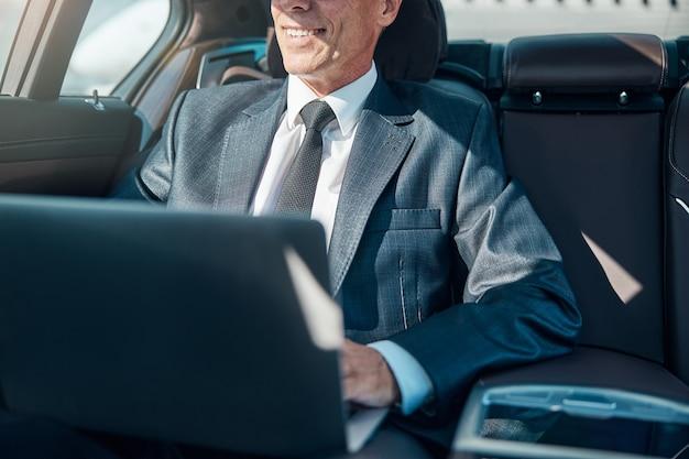 Bijgesneden hoofd van een gelukkige zakenman die een notebook gebruikt terwijl hij door de chauffeur wordt vervoerd na de landing op de luchthaven