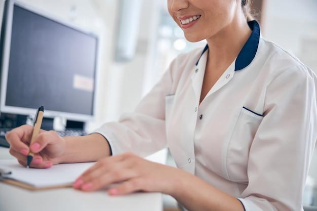Bijgesneden hoofd van een vrolijke jonge vrouw die aan een bureau zit met een computer en een recept schrijft
