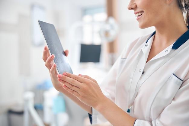 Bijgesneden hoofd van een vrolijke jonge vrouw die in een modern kantoor staat en een digitale tablet vasthoudt terwijl ze naar het scherm kijkt