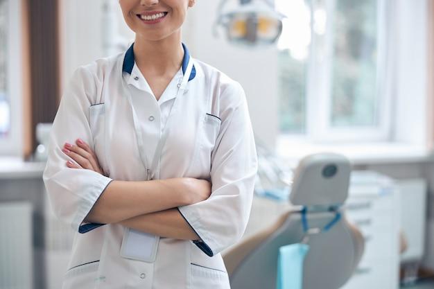 Bijgesneden hoofd van lachende jonge vrouw in medisch uniform die in de buurt van de tandartsstoel staat en op patiënten wacht