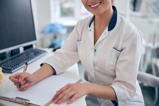 Bijgesneden hoofd van lachende vrouw in medisch uniform die aantekeningen maakt op papier terwijl ze aan tafel zit met de computer