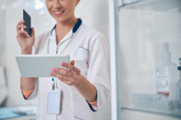 Bijgesneden hoofd van vrolijke jonge vrouw die smartphone en touchpad vasthoudt terwijl ze in de tandheelkundige kliniek staat