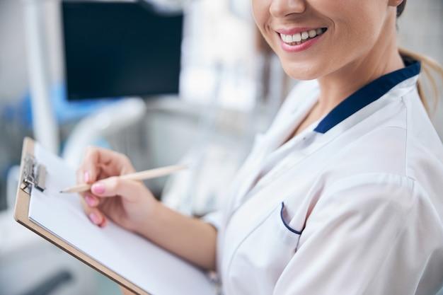 Bijgesneden hoofd van vrolijke mooie vrouw die in de buurt van de tandartsstoel staat en aantekeningen maakt over de gezondheid van de patiënt patient