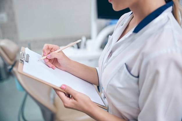 Bijgesneden hoofd van vrouw in medisch uniform die klachten van patiënten opschrijft tijdens bezoek aan kliniek