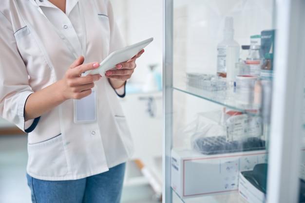 Bijgesneden hoofd van vrouw in wit uniform dat in de buurt van planken staat met medicijnen en tablet vasthoudt