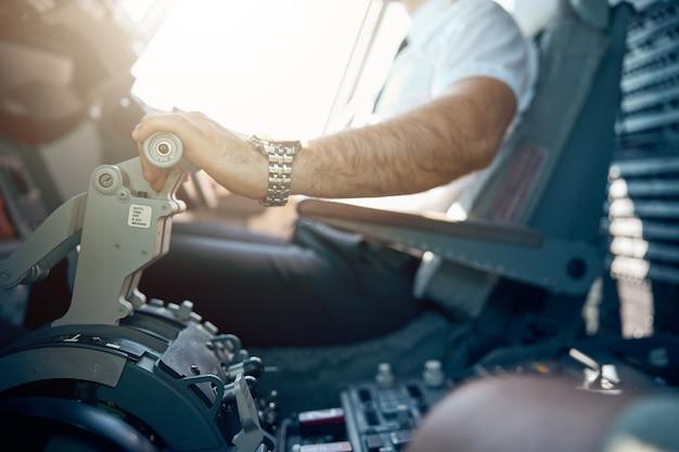 Bijgesneden hoofdportret van de hand van een europese piloot die een commercieel vliegtuig bestuurt
