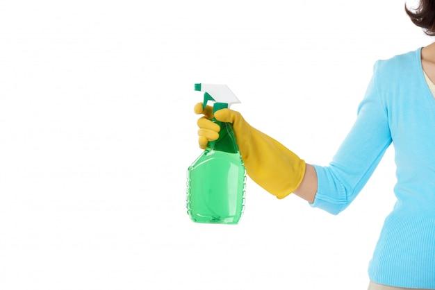 Bijgesneden huishoudster staat met gestrekte hand en houdt de reinigingssprayfles vast