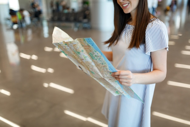Bijgesneden jonge lachende reiziger toeristische vrouw met papieren kaart zoeken route tijdens het wachten in de lobby hal op de internationale luchthaven