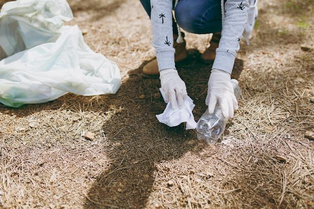 Bijgesneden jonge vrouw in vrijetijdskleding, handschoenen schoonmaken van afval in vuilniszakken in park