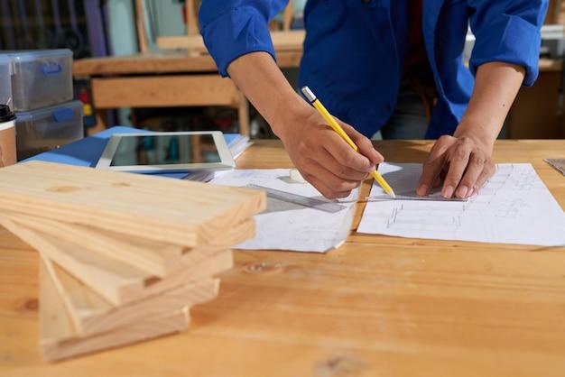 Bijgesneden man met blauwe overall tekenmeubels op het vel papier