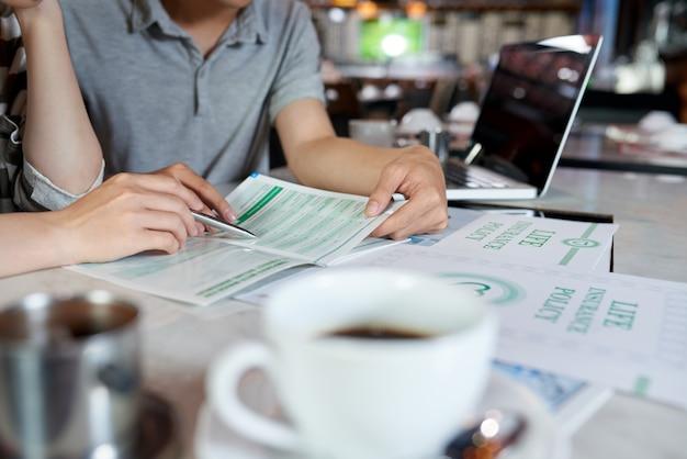Bijgesneden mensen die levensverzekeringsbrochure bestuderen