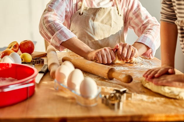Bijgesneden moeder leert dochter om het deeg uit te rollen voor het bereiden van lekkere koekjes, koekjes thuis. bakkerij concept
