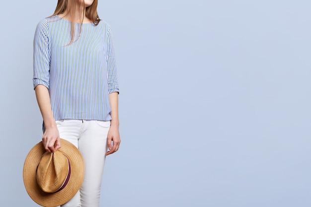 Bijgesneden onherkenbaar vrouwtje gestreepte blouse en witte broek, houdt strooien hoed, draagt modieuze kleding, geïsoleerd op blauw met kopie ruimte voor uw advertentie.