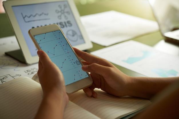 Bijgesneden onherkenbare persoon die financiële grafiek op smartphone analyseert